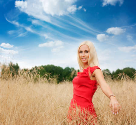 Smiling Blonde Woman in Red Dress Standing in the Field