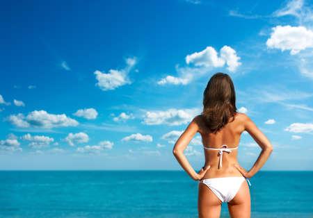 Donkerbruine Vrouw in bikini te zonnen op zee.