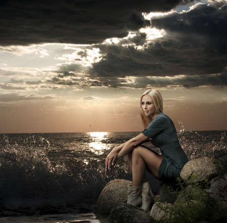 Fashion Photo of Blonde Woman on the Rock near the Stormy Sea Stock Photo - 15441141