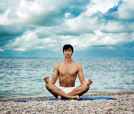 Young Man Practicing Yoga near the Ocean Stock Photo - 15563054