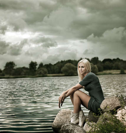 Photo of Blonde Woman on the Stone near the Lake Stock Photo - 15851162