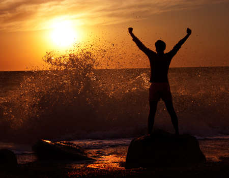 victory stand: Silhouette of Man with Raised Hands at Stormy Sea  Freedom Concept  Stock Photo