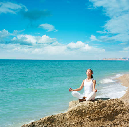 Young Woman Practicing Yoga near the Ocean Stock Photo