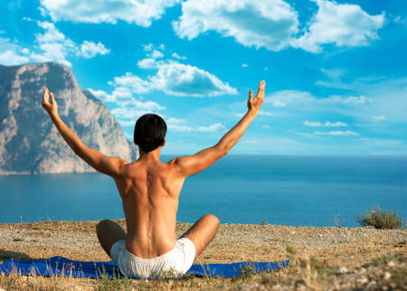 Young Man in Lotus Position near the Ocean  Rear View Stock Photo