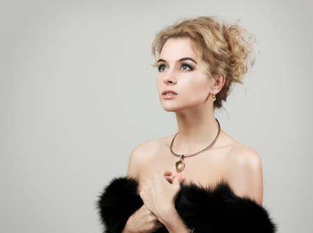 Portrait of Stylish Woman in Fur against Grey Background