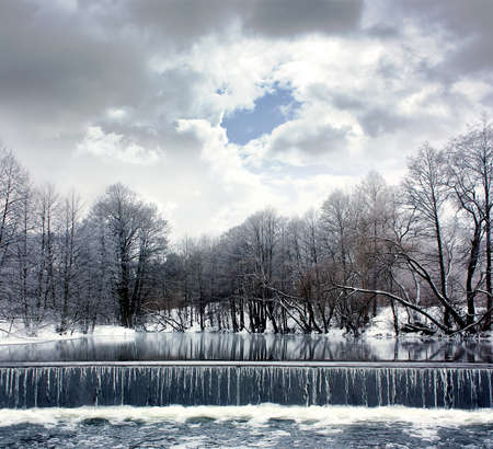 Winter Landscape with Calm River, Waterfall and Moody Sky