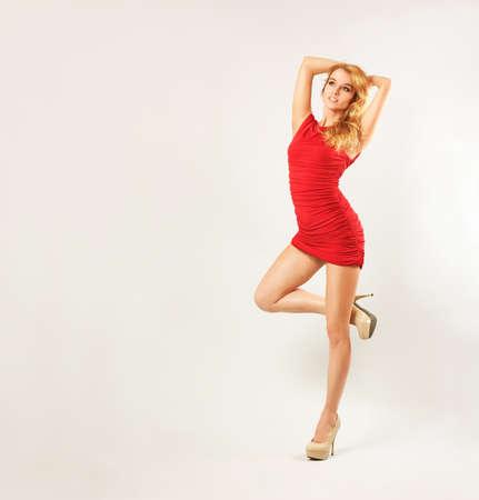 tacones rojos: Retrato de cuerpo entero de una mujer rubia atractiva en vestido de moda rojo Foto de archivo
