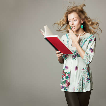 thrill: Surprised Blonde Woman Reading a Book on Gray Background  Copy Space