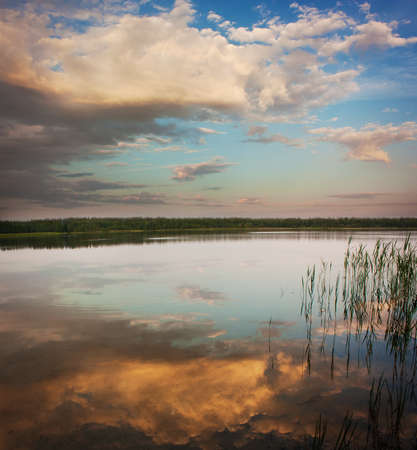 Landscape with Calm Lake at Sunset with Beautiful Clouds Reflection