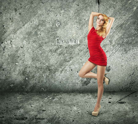 Full Length Portrait of a Sexy Blonde Woman in Red Fashion Dress against Concrete Wall Stock Photo