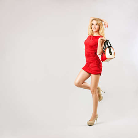sexy blonde girl: Full Length Portrait of a Sexy Blonde Woman in Red Fashion Dress with Bag