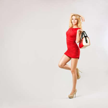 sexy beine: Full Length Portrait von einem Sexy blonde Frau im roten Kleid mit Tasche