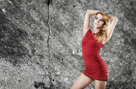 Portrait of a Sexy Blonde Woman in Red Fashion Dress against Concrete Wall Stock Photo - 19025431