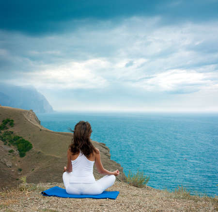 Young Woman in Lotus Position near the Ocean  Rear View Stock Photo