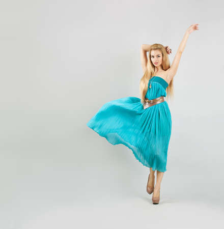 Full Length Portrait of a Sexy Blonde Woman in Turquoise Fashion Dress Stock Photo
