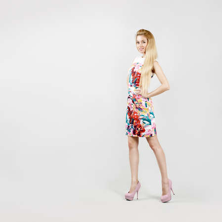 Full Length Portrait of a Sexy Blonde Woman in Colorful Fashion Dress Stock Photo
