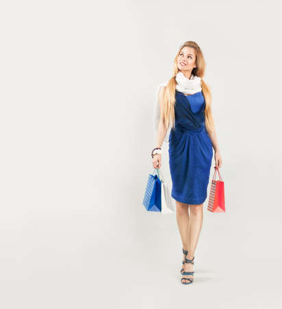 Full Length Portrait of a Blonde Woman in Blue Fashion Dress with Shopping Bags photo