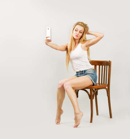 Playful Sexy Woman Taking Self Portrait with Smartphone photo