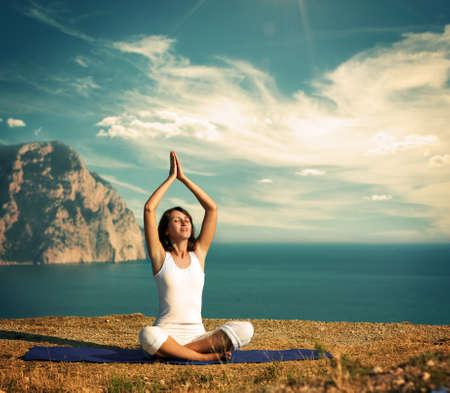 mujer meditando: Mujer joven en posición de loto cerca del estilo de la vendimia del océano
