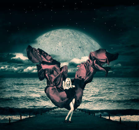 Sexy Woman Standing on a Pier with Waving Fabric  Fantasy Background with Rising Moon