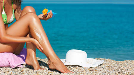 Woman Applying Sunscreen Lotion on Her Sexy Legs at Beach