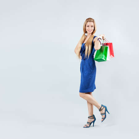Full Length Portrait of a Blonde Woman in Blue Fashion Dress with Shopping Bags