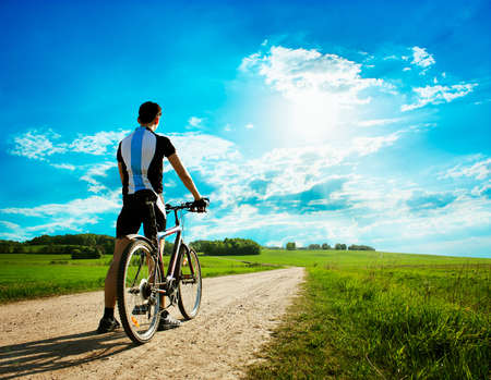 Rear View of a Young Man With Bicycle on Summer Nature Background  Healthy Lifestyle Concept  Copyspace  photo