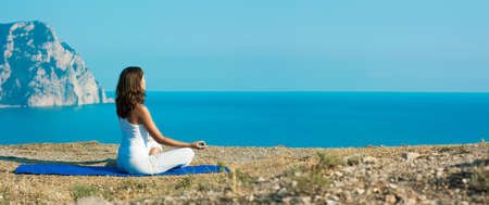 Young Woman Doing Yoga in Lotus Position at the Sea and Mountains  Panoramic View