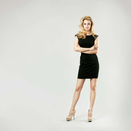 Full Length Portrait of a Sexy Blonde Woman in Little Black Fashion Dress photo