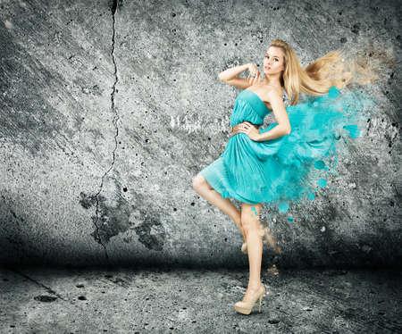 Sexy Woman in Splashing Dress on Concrete Wall Background