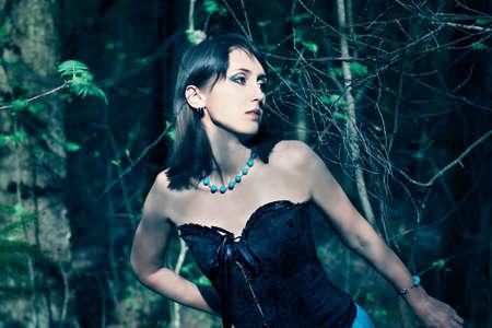 Fashion Portrait of Beautiful Woman in Dark Forest
