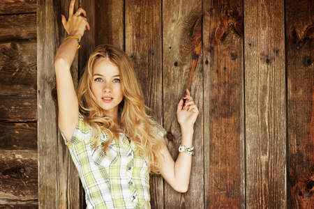 Portrait of Beautiful Blonde Woman on Wooden Wall Background
