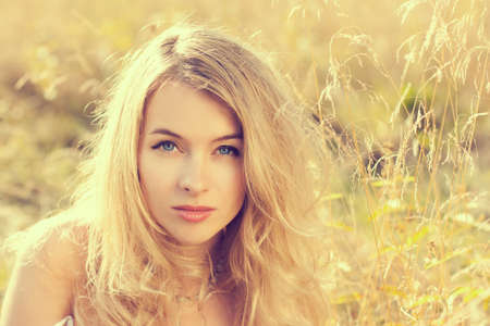 Portrait of Beautiful Blonde Woman at Summer Field Stock Photo