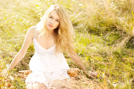 sundress: Beautiful Blonde Woman Sitting at Summer Meadow in White Sundress Stock Photo