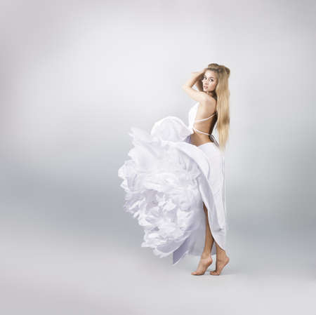 Blonde Woman in White Peony Flower Dress on Gray Background Stock Photo