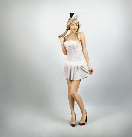 Full Length Portrait of a Sexy Woman Wearing a Bunny Costume with Rabbit Ears on Gray Background photo