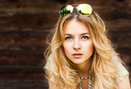 木製の壁の背景に美しい金髪女性の肖像画