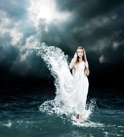 Woman in Splashing Dress Walking on Stormy Sea. Aphrodite Godess Collage. Stockfoto