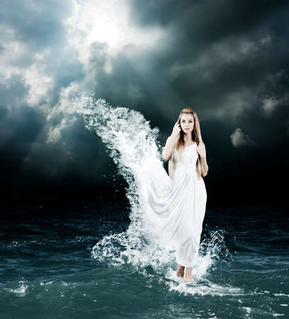 Woman in Splashing Dress Walking on Stormy Sea. Aphrodite Godess Collage. Фото со стока