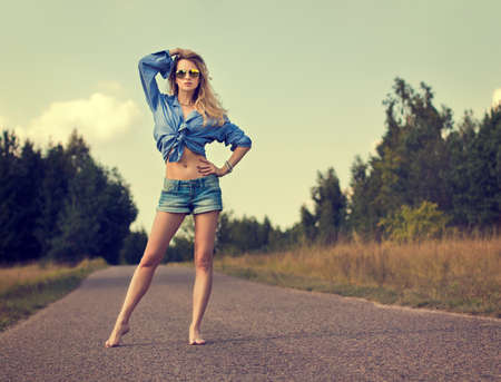 Full Length Portrait of Sexy Blonde Woman Standing on the Road
