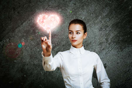 Beautiful Woman Pointing at Glowing Pink Heart. Perfect Valentines Day Concept.