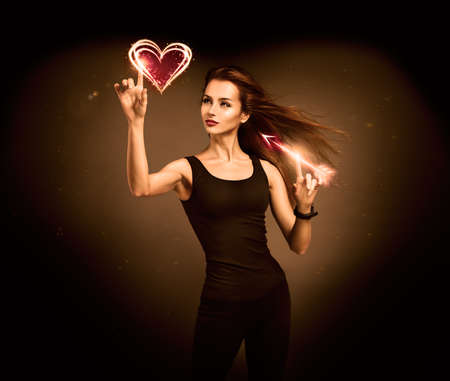 Sexy Woman Aiming to the Glowing Heart with an Arrow on Dark Background  Fantasy Cupid Concept for Valentine photo