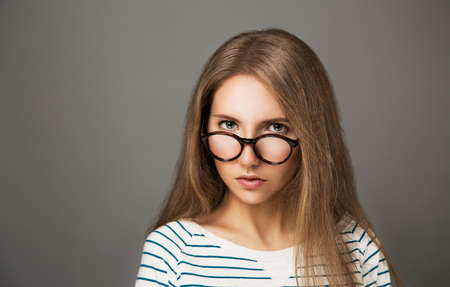 Studio Portrait of Serious Hipster Girl in Trendy Glasses photo