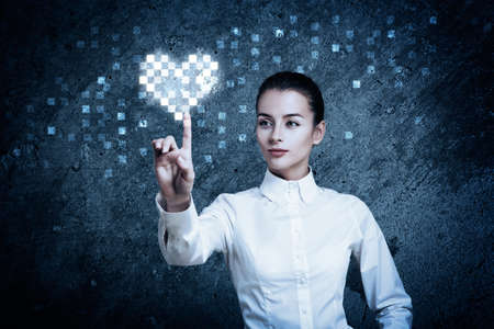 Beautiful Woman Pointing at Glowing Digital Heart. Perfect High Tech Valentines Day Concept.