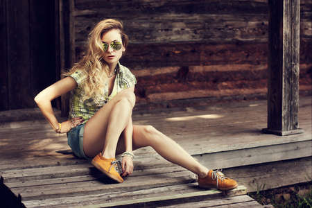 Trendy Hipster Girl Sitting on the Wooden Porch. Toned Photo. Modern Youth Lifestyle Concept. photo
