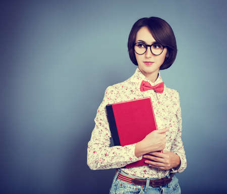 Retro Portrait of Trendy Hipster Girl Wearing Glasses, Shirt and Bow Tie photo