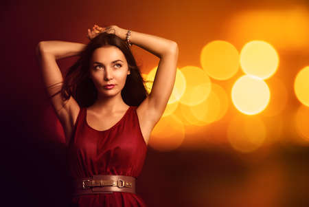 night out: Portrait of a Beautiful Young Woman in Fashionable Red Dress over Bright Night Lights
