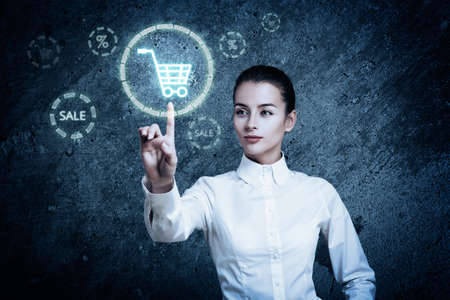 hightech: Beautiful Woman Pointing at Glowing Shopping Cart Icon