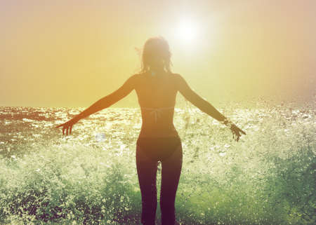 Beautiful Woman in Bikini Standing in the Sea Waves and Enjoying Sunshine with Open Arms