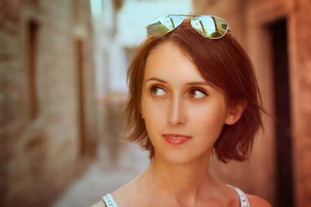 Toned Portrait of Trendy Young Woman with Bob Hairstyle in the Old Street  Filtered Photo with Shallow Depth of Field  photo